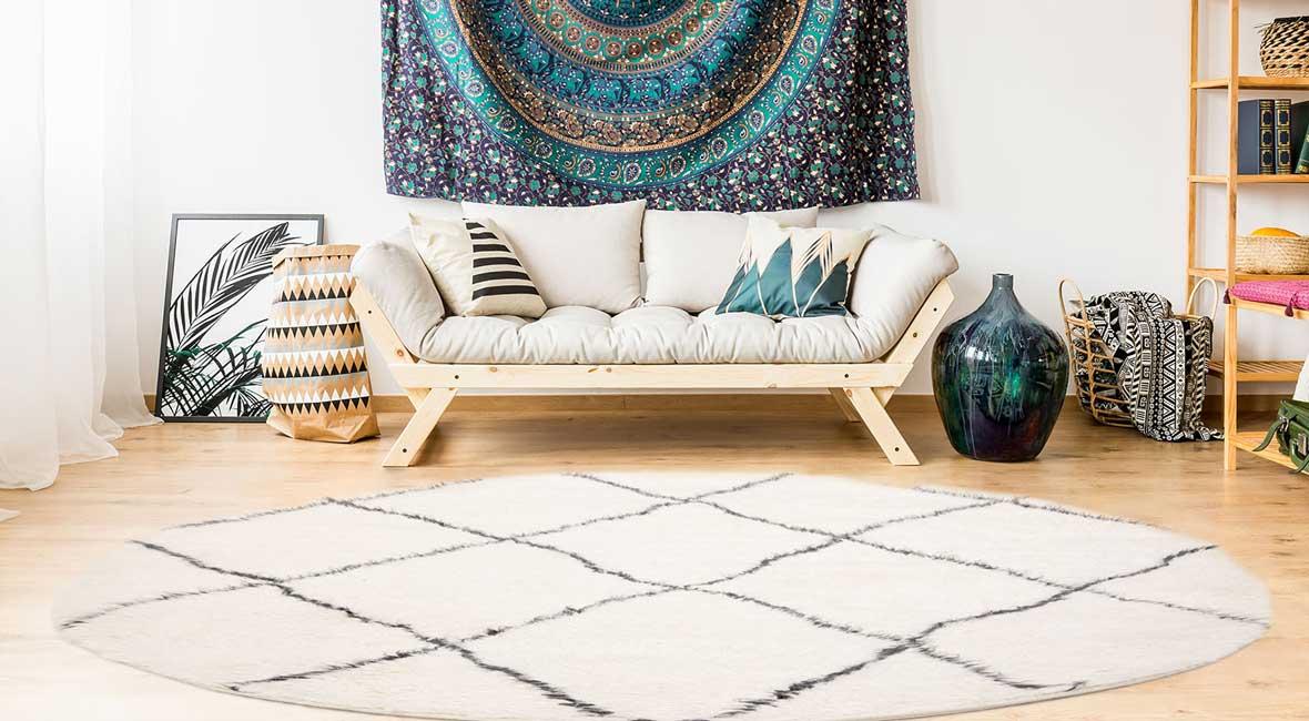 Bilden visar hur ett litet rum kan se större ut genom att möblera med en rund matta.