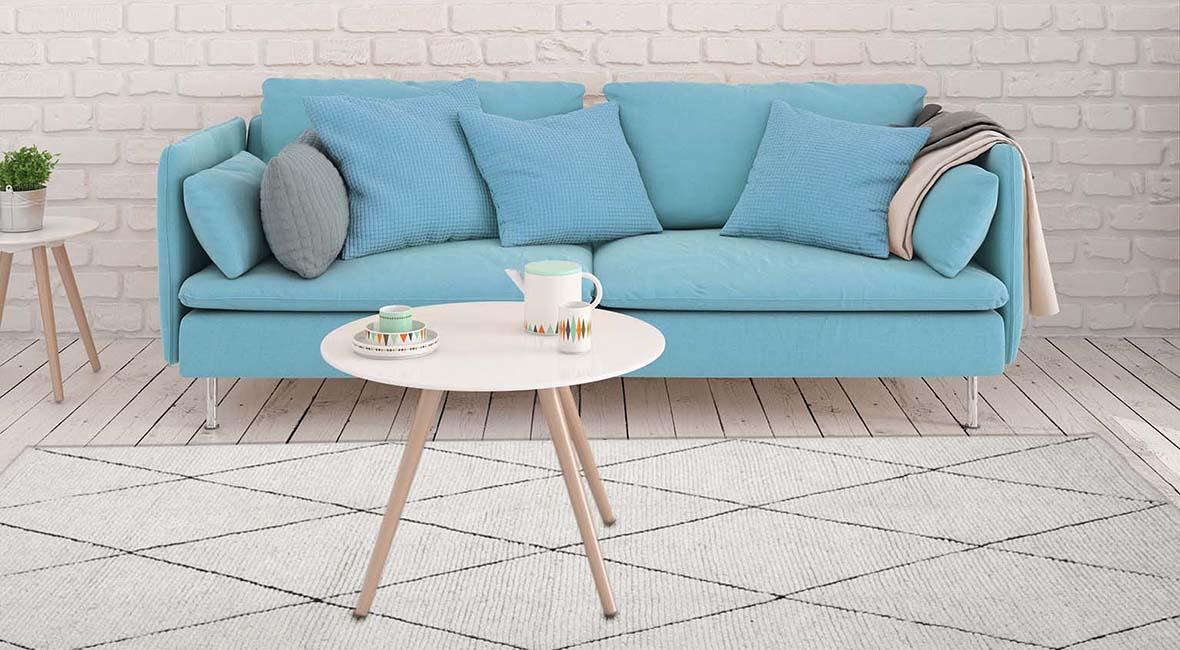 Soffgrupp med en fristående matta. Endast soffbordet står på mattan.